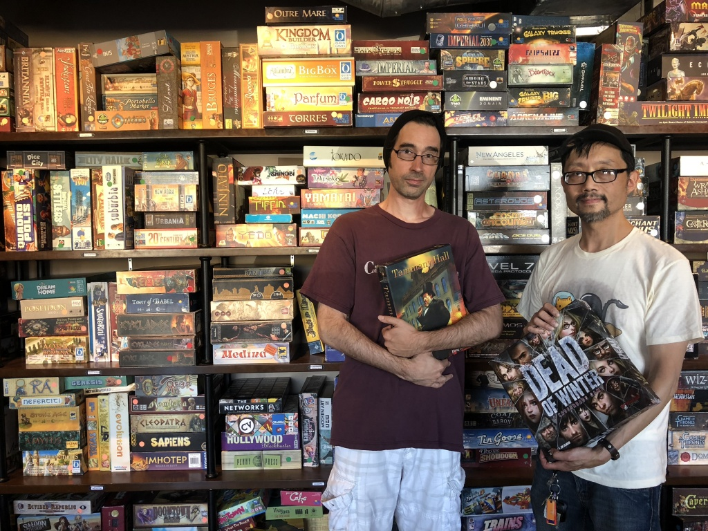 Game Haus co-owner Rob Cron and Terry Chiu holding two of their favorite games - Tammy Hall and Dead of Winter.