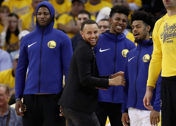 Stephen Curry #30 of the Golden State Warriors reacts on the bench with Nick Young #6, Jordan Bell, and Quinn Cook #4 during Game Five against the San Antonio Spurs of Round One of the 2018 NBA Playoffs at ORACLE Arena on April 24, 2018 in Oakland, California.