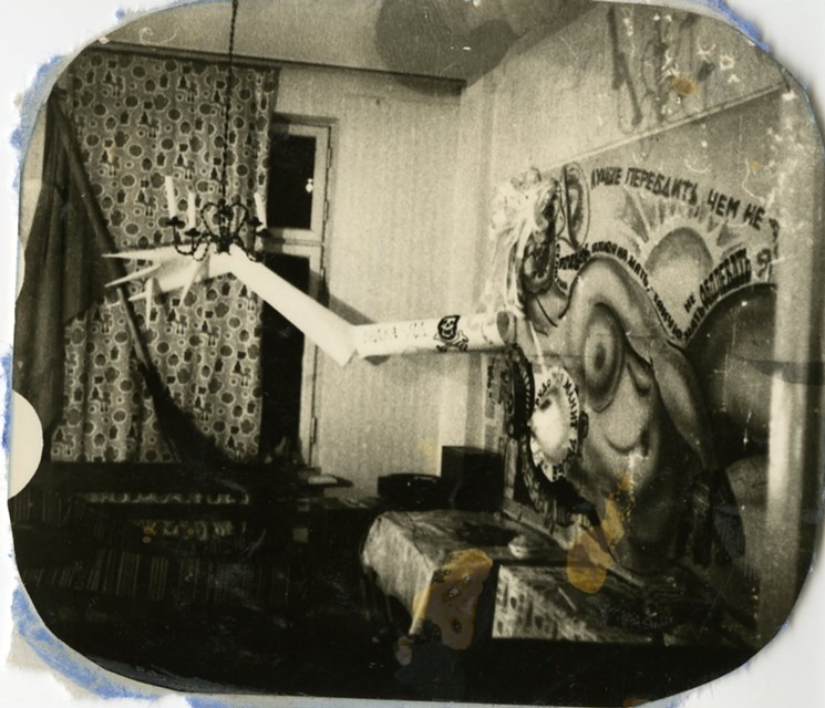 Moscow hippie apartment interior with a wall-sized picture of a naked woman with extended cardboard arm, 1975